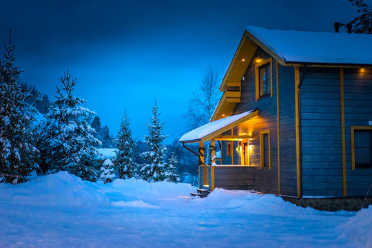 Snow-covered cottage. Wooden two-storey cottage. Winter.