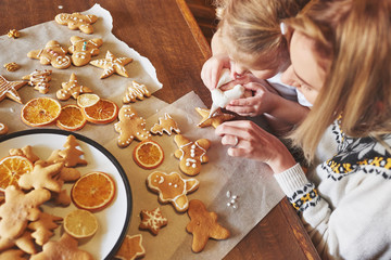 Mom and daughter decorate the Christmas cookie with white sugar