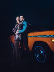 Young couple near yellow taxi car in night time