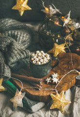 Christmas or New Year winter hot chocolate with marshmallows, gingerbread cookies and cinnamon sticks over wooden board served with holiday light garland and grey sweater, selective focus
