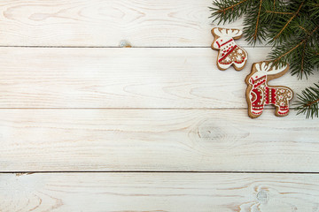 Overhead of Christmas New Year holiday background. Red gingerbread cookies deer and elk and fir branch tree on white wooden table. Top view.