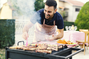 Young man making barbecue