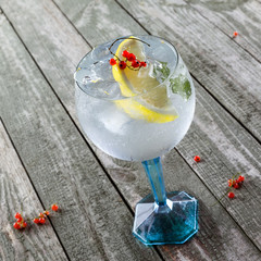 Delicious gin and tonic cocktail on a wooden table. Alcoholic drink in a glass.