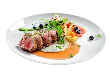 Delicious medium rare meat steak with sauce and salad on a plate. Healthy food made of meat fillet and fresh herbs isolated on a white background.