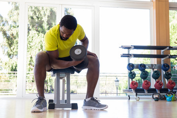 African-American man sitting on bench in gym and lifting heavy dumbbell.