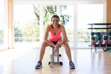 Beautiful woman in sportswear sitting on bench in gym near dumbbell, looking at camera and smiling.