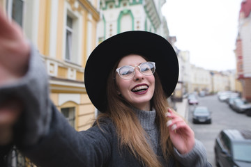 Stylish girl with braces takes selfie krasvoho against the background of the urban landscape. The girl tourist on background makes selfie beautiful streets of the old town.
