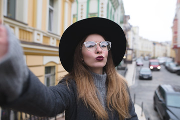 Stylish girl takes selfie street while walking around the beautiful city. Tourist hipster posing for the camera of your phone and make selfie.