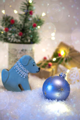 Christmas or new year card . Cookies in the shape of a dog. New year bright decoration and presents  on light background with lights.