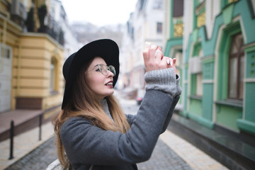 Stylish tourist girl photographs a beautiful old town on the phone. Mobile photography. The blogger photographed the city