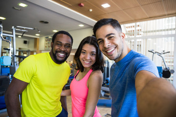 Group of people in sportswear standing in gym, smiling and taking selfie.