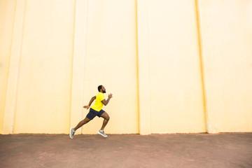 African-American man running fast near beige wall.