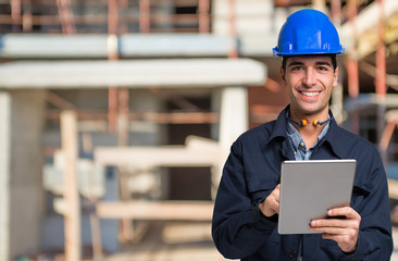 Worker using a tablet in front of a construction site