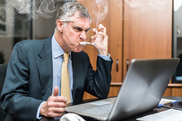 Nervous businessman smoking many cigarettes at once