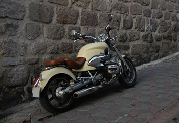 old cream colored vintage  motorcycle parked in old downtown street in front of a rock wall