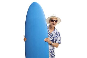 Elderly tourist holding a surfboard