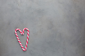 Heart of two red-white candy canes on the gray concrete background. Beautiful background. Flat lay, top view