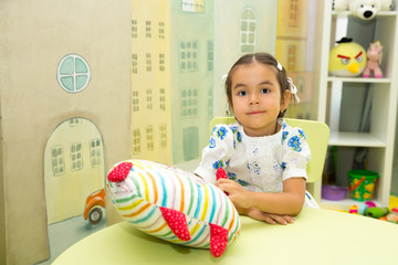 Adorable asian, Kazakh child girl in nursery room. Kid in kindergarten in Montessori preschool class.