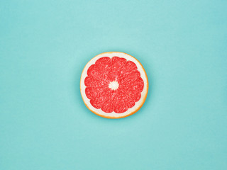 Grapefruit in flat lay Half of ripe grapefruit is lying on light-blue background Top view Modern bright flat lay photo mockup with space for text