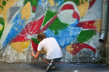 Photo of a young guy in denim shorts and a white shirt. The guy draws on the graffiti wall a drawing with aerosol paints of various colors. The concept of hooliganism and damage to property