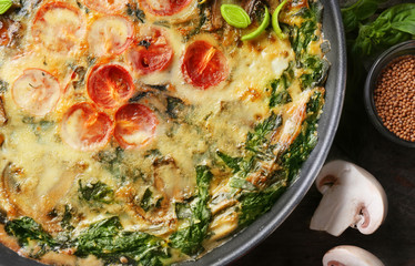 Frying pan with delicious spinach frittata on table, closeup