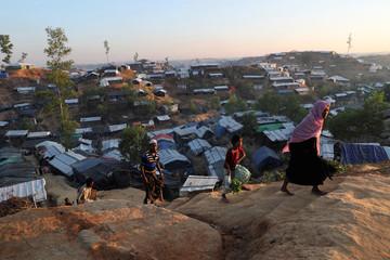 Rohingya refugees walk along the road of the Balukhali Refugee Camp in Cox's Bazar