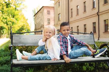 Cute fashionable children sitting on bench outdoors