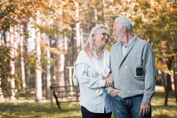 Happy senior couple smiling outdoors in nature, having fun