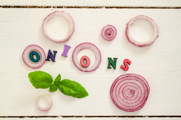 The word ONIONS among slices of red onions