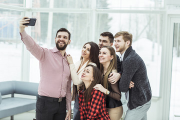 friendly business team taking a selfie while standing near window in office
