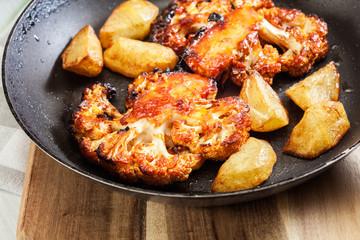 Vegetarian roasted cauliflower steak with herbsand fried potatoes