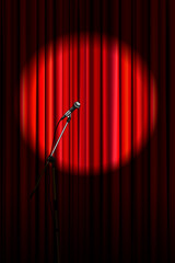 Bright red curtain with microphone in round spotlight lighting, retro theater stage vertical background