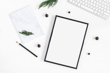Christmas desk. Black frame, keyboard, marble notebook and christmas tree branches on white background. Flat lay, top view, copy space
