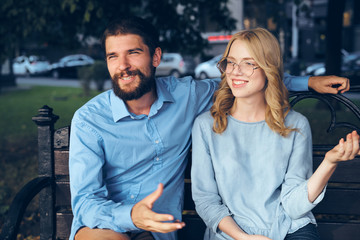 A man and a girl on a bench smile against the background of the city