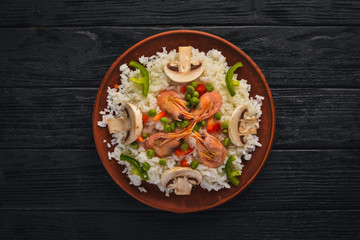Risotto with shrimp and vegetables. Seafood. Asian cuisine. On a wooden texture background. Top view. Free space.