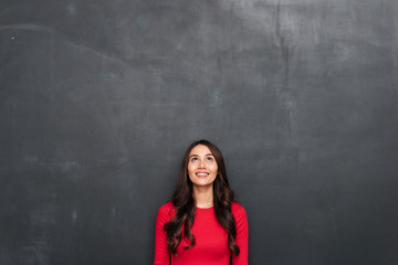 Picture of Happy brunette woman in red blouse looking up