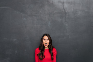 Picture of surprised brunette woman in red blouse
