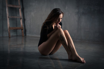 photo of a beautiful girl who sits in a dark room cold wet my sad and scary background of the ladder