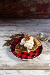 pecan pie slice with vanilla icecream in festive setting