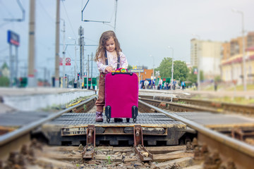 Little girl stay on the rails on railway station.