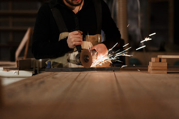 Industrial worker cutting metal with many sharp sparks. Selection focus to cutting machine. Copyspace. Place for the text. dark lighting