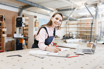 Businesswoman carpenter working on laptop on wooden surface among construction tools. Nearby is smartphone, laptop ,clipboard. Online education. startup business. young specialist designer.