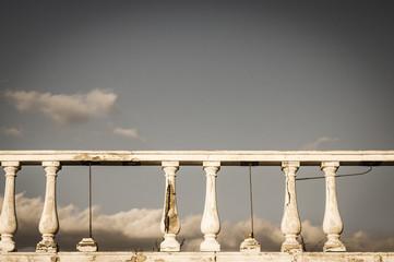 Damaged balustrade on clouds sky background