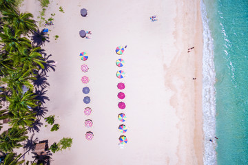 Top view of beach with colorful umbrellas and people bathing in El Nido, Palawan, Philippines.