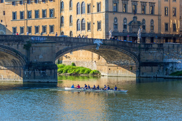 Rowing boat on the river at an old bridge in Florence