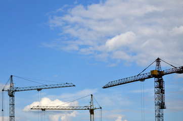 Tall and heavy construction crane towers against a blue sky
