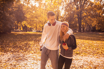 Young couple walking at the park ,relaxing after jogging.Cold and sunny autumn day.