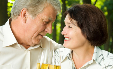 Senior couple celebrating with champagne, outdoors