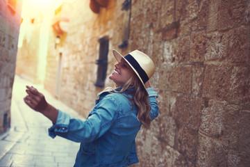 Young carefree woman walking on mediterranean street