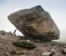 Man with pushing a huge stone in Ergaki mountains, Russia